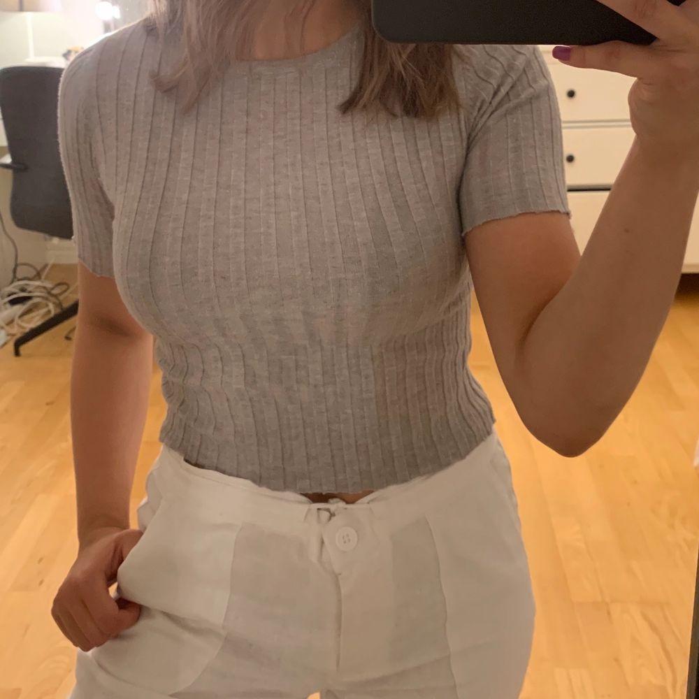 Säljer en grå trekvartslång t-shirt. I storlek xs/s🖤. Toppar.