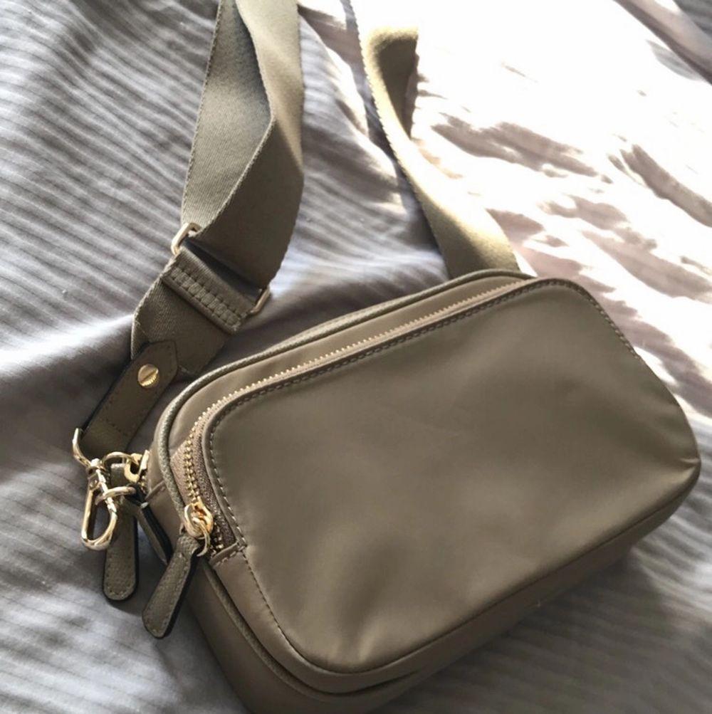 Helt ny axelremsväska från hm. Färgen på väskan är beige och har mycket utrymme. Finns två fickor med förvaring. . Väskor.