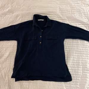 Mörkblå skjorta med bruna knappar och bröstfickor i linnetyg. Köpt från Zara i strl S. Använd 1 gång.