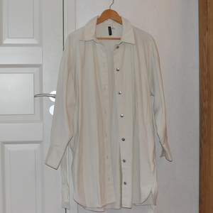 En längre skjorta som kan användas öppen och stängd. Den är i storlek m, skulle kunna passa L, eller vara oversized på mindre storlekar. Väldigt fint skick, bara provad. Den kan knytas i midjan med tillhörande band. Skicka om du vill ha fler bilder.