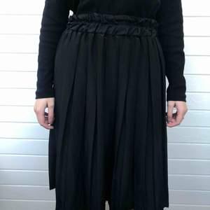 Veckad kjol från Gulins i glansigt tyg. Den är i 42/44 men den tidigare ägaren har 38. Den är i bra begagnat skick och har inga fläckar eller hål. Den är gjord i Storbritannien. Den är gjord i 100% polyester.   Personen på bilden är 158 cm lång.