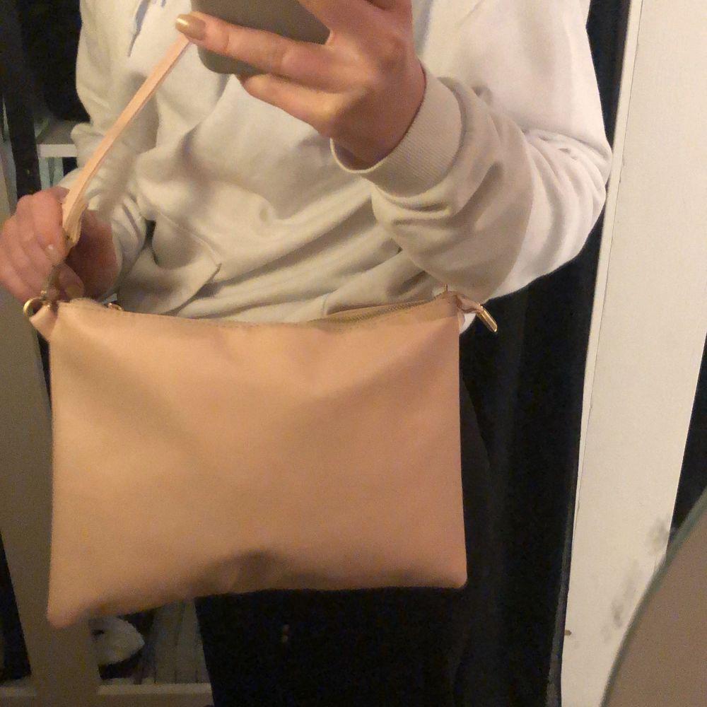 Snygg ljusrosa väska från boohoo! Guld detaljer och man kan ändra bandet. Används inte så därför säljer jag den. . Väskor.