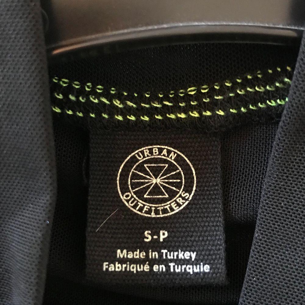 """Mesh top med texten """"BABYGIRL"""" från Urban Outfitters! Gröna neondetaljer längs sömmarna och en kort polo krage. Köpt förra sommaren, jättebra skick. Rekommenderar att ha ett linne under (som på bilden) då den är lite genomskinlig. GRATIS FRAKT💕☺️. Toppar."""