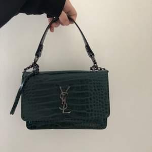 Jättefin krokodilmönstrad YSL look-a-like i mörkgrönt. Köpt på cypern förra året, använd några gånger men den har inte helt fått den kärleken den förtjänar, därför söker den nu ett nytt hem!