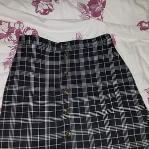 Kortare svart- och vitrutig kjol i storlek 40, bra passform och inte för stor. Har använts endast ett fåtal gånger och är därmed i fint skick.