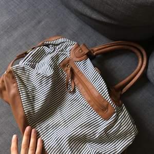 Rymlig väska i blåvitrandigt tyg. Använt som datorväska men passar säkert jättebra till stranden nu i sommar!