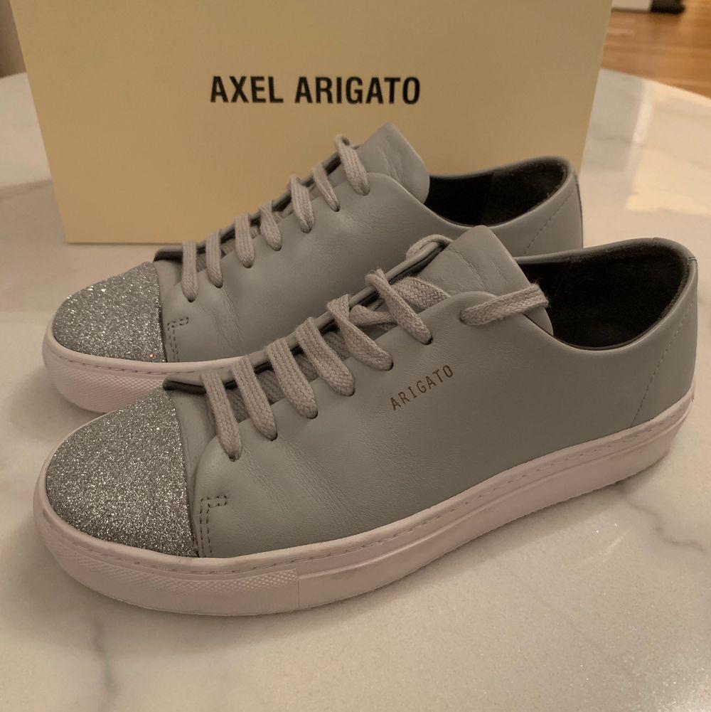 Ljusgrå sneakers från Axel Arigato med silverdetaljer längst fram. Storlek 37! Använda 1-2 ggr. . Skor.
