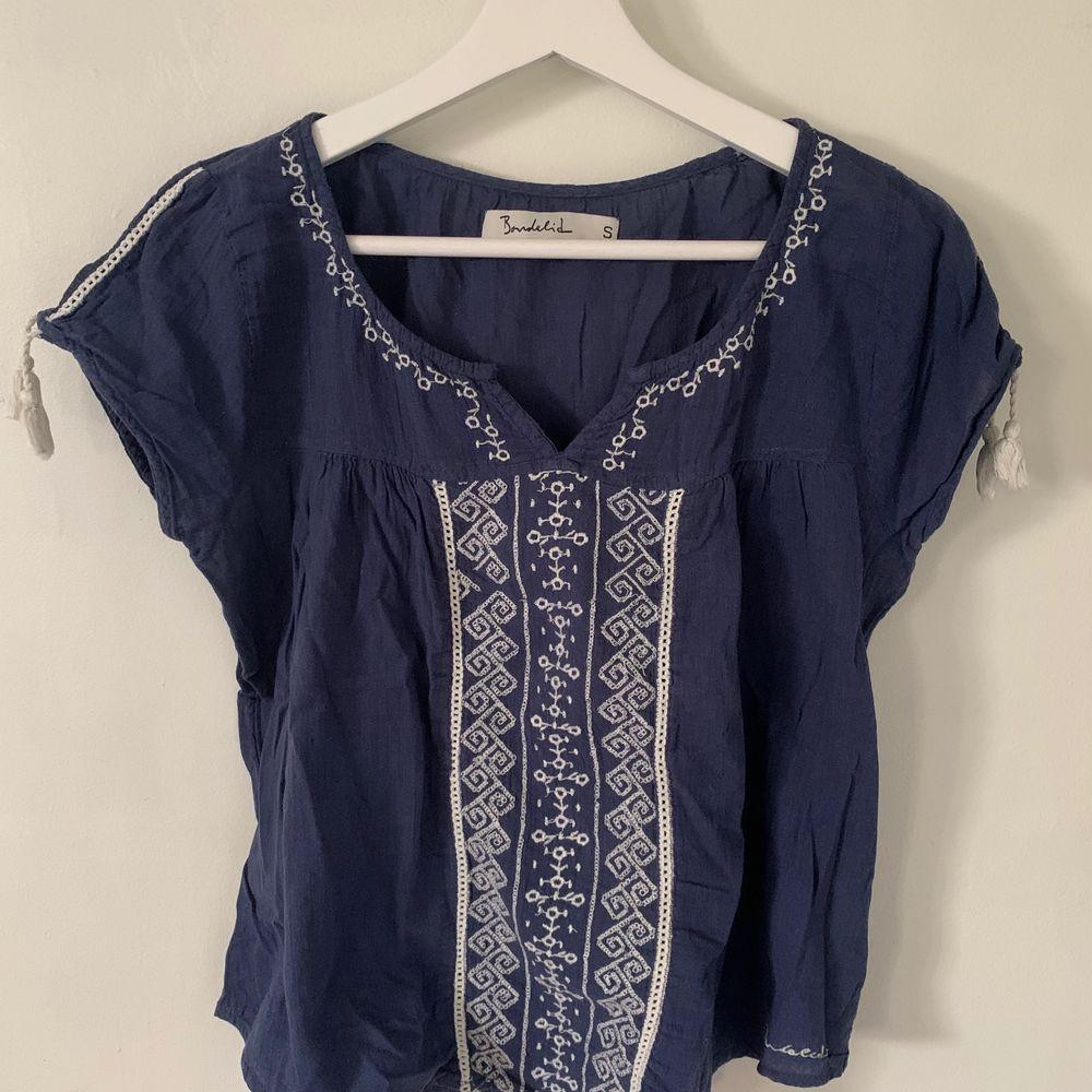 """Jättefin blå blus med lite vita detaljer. Lite """"bohemian"""" stil💘. Storlek S men passar även M då den är lite pösig. Söta tofsar på ärmarna💖. Köparen står för frakten😋. Blusar."""