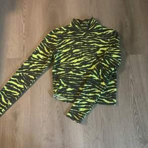 Långärmad tröja med liten krage och tiger mönster i lime grön och svart. Använd ett par gånger men fortfarande bra skick. 😄 frakt diskuteras privat