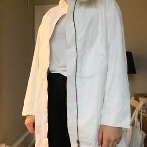 Vit regnkappa från Zara med silvrig dragkedja. Storleken är XL men passar även mig som vanligtvis har S-M i jackor. Kan mötas upp centralt i Göteborg. Annars står köparen för frakt! <3                                                                                                                            (Säljer just nu massa fler kappor och jackor så kolla gärna in min profil!)