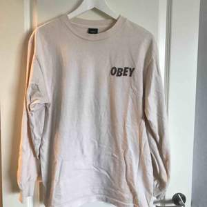 Sjukt snygg tröja från Obey med ballt, trippy tryck på ryggen. Fin ljusbeige färg. Nyskick. Köpt för 899kr.