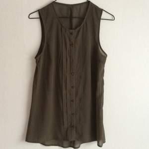 Mörkgrönt transparent linne från vila.  Bortklippt lapp och en knapp saknas.  Använt en gång.