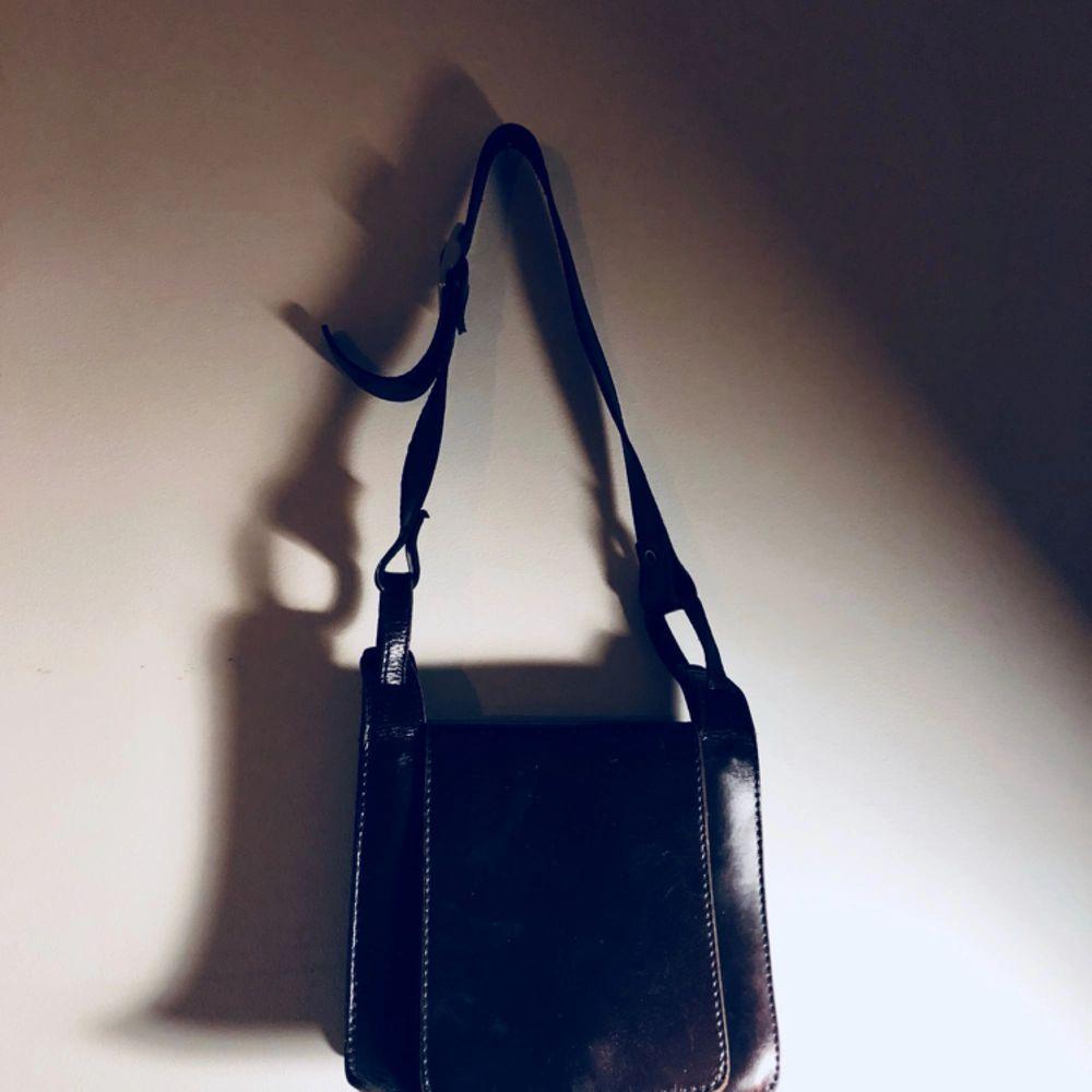 Mörkbrun axelremsväska köpt secondhand! . Väskor.