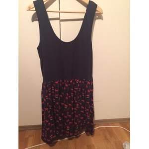 Marinblå klänning med dragkedja i ryggen med hästmönster på kjol delen.  Använd 2 gånger.  OBS! Ska plagget fraktas står köparen för den här kostnaden