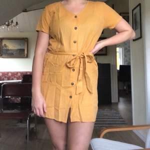 """Gul/senapsgul klänning från NAKD, knappar fram och band i midjan. """"Linen look buttoned dress"""" linneliknande material. Storlek 40."""
