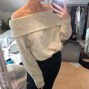 En beige stickad offshoulder tröja från H&M i storlek XS.