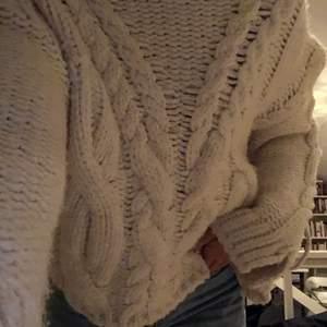 Vit grovstickad tröja med detaljer, snördetalj på båda ärmarna. Kontakta vid intresse