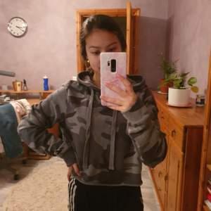 En grå hoodie med kamouflage. Croppad och från Hollister. Skriv i dm vid frågor eller intresse