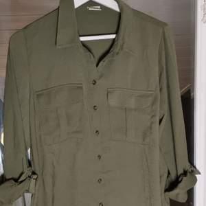 Militärgrön skjorta med coola detaljer från JACQUELINE de YONG i storlek 36.