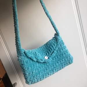 Virkad shoulderbag med mysigt garn. Väskan är ca 14x23 cm. Längd på banden får man bestämma själv. (Tar emot bud om det är flera men minst 200 kr). Frakt kan diskuteras.