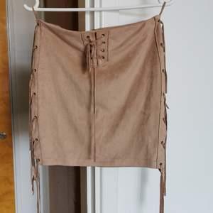 Snygg kjol i fakemocka med fransar fram och på sidorna. Dragkedja bak.