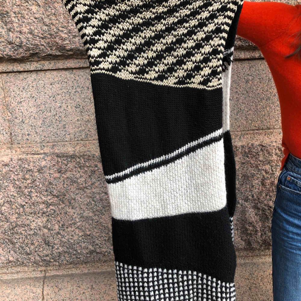 Knitted stretchy long scarf. White and black with gold accent. Stickat.