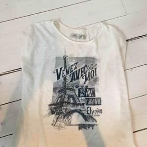 Vit, lite krämvit, t-shirt från Abercrombie med blått paris-tryck och lite paljetter-isch. Storlek XS, passar även S, använd men i superfint skick. Mjukt tyg, nypris ca 500 kr