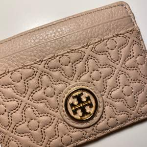 """Så fin korthållare från Tory Burch. Den är i läder och har ett """"blommigt"""" mönster i en superfin rosa/beige färg. Köpt för ca 2 år sedan men aldrig använd. Hittade en liknande korthållare på sista bilden för 1 499kr (eftersom jag ej har kvitto kollade jag upp det). Äktighets siffror finns i!💕"""