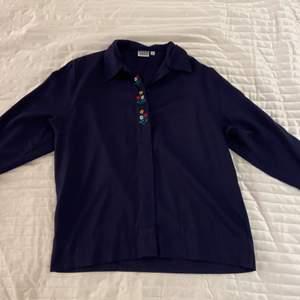Mörkblå skjorta med broderade blommor. Från No1 i strl 36. Aldrig använd.