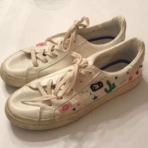 Ett par vita skor i storlek 38 med broderade symboler på sidorna från ZARA. I använt skick! Kan mötas upp i centrala Uppsala alt. Köparen står för frakt!