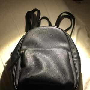 Jätte söt liten svart mini ryggsäck med guld detaljer. Knappt andvänd och från början från primark i super fint skick. !möts bara upp!