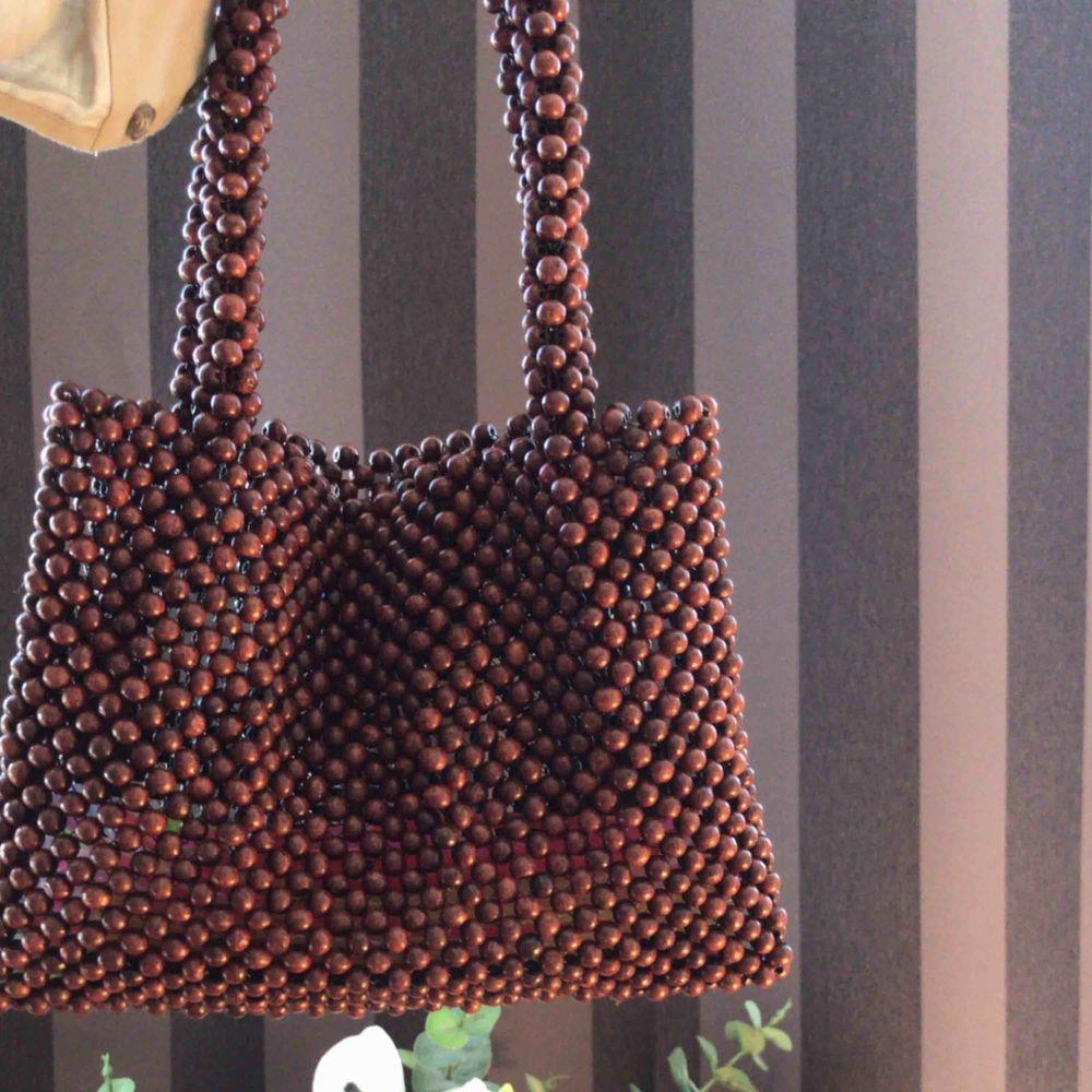 Säljer min söta lilla väska från Na-Kd, den är gjord av träkulor (typ), helt ny har kvar lapparna tillomed tror jag, runt 500 nypris💜💞. Väskor.