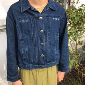 Jättesöt jeansjacka med fina knappar och blomsterdetaljer. Lös och följsam i passformen. Säljer då jag tyvärr inte använder den så mycket. Köpt second hand men är i jättefint skick!🌸 frakt inkluderat.