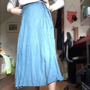 Fin blå kjol som man knyter i midjan. Tyget faller jättefint och kjolen går att anpassa till alla storlekar❣️
