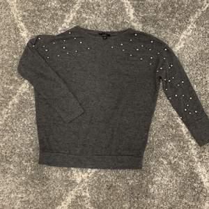 Grå långärmad tröja med små silvriga kulor på ärmarna. En snygg detalj!