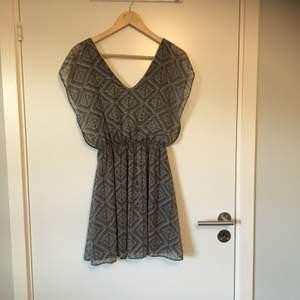 Mönstrad klänning i svart och vit med guldfärgade detaljer från Vintage Love. Stl XS eller möjligtvis S, lapp saknas. Gott skick, knappt använd. Frakt betalas av köparen.