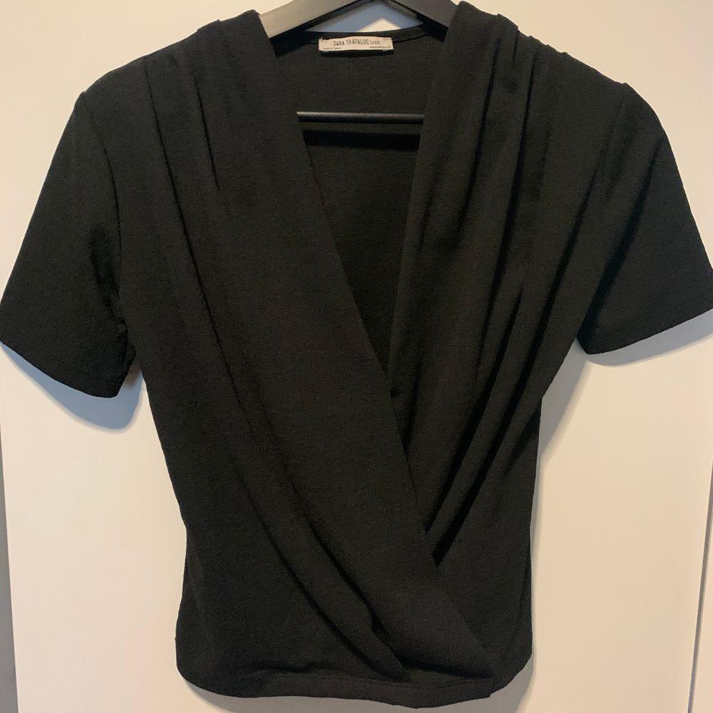 Svart topp med omlott från Zara, helt i nyskick då den aldrig kommit till användning!. Toppar.