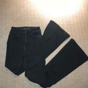 Svarta bootcut jeans från Bershka med hål på båda knäna. Jeanstyget är stretchigt och formar sig fint efter kroppen. Byxorna är använda, men fortfarande i fint skick.
