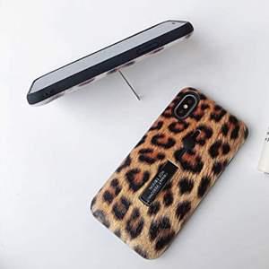 """Ett iPhoneskal för 7/8 med leopardprint. Metall på baksidan kan vikas ut för att ge mobilen stöd. Bandet med texten """"I want personality not trival"""" kan man lätt dra ut med hjälp av den neddragbara knappen ovan för att mobilen ska vara säker i handen."""