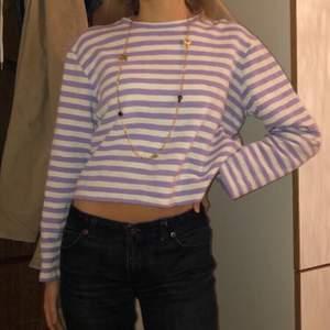 randig lila/vit halvcroppad långärmad tröja i ett halvtjockt material. formen och ärmarna är breda och halsen ganska högt skuren, cool att ha med t.ex en vit t-shirt över
