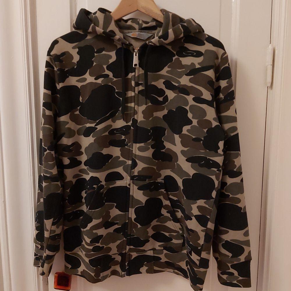 En zip hoodie från carhartt med camo-mönster. Super skön och oversized men använder inte längre. Är i storlek herr M, jag har vanligtvis dam S. Passar säkert upp till L beroende på önskad fit.. Huvtröjor & Träningströjor.