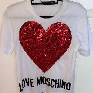 En superfin T-shirt från märket Moschino. Ett stort rött glittrigt hjärta på framsidan och Love Moschino står även undertill. Endast använd en gång då det inte riktigt är min stil. Storlek 36. Pris= 200+ frakt!
