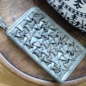 Större clutch/plånbok i grått genuint skinn med flätad framsida och två dragkedjor och flera fack inuti. Ett fack med dragkedja på baksidan. Från danska By Burin. Nypris 1299:-