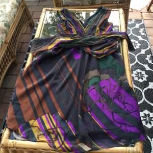 Festklänning i läckra färger matrial silke dragkedja i sidan 32 cm lång tunt foder i svatt v- ringad fram och bak knytband bak kjolens vidd är 1.50 cm hela klänningens längd 1.08 kemtvätt fint skick nypris 1400:- tar swish