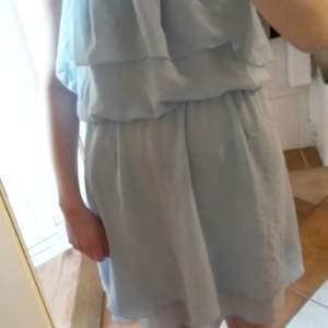 Fin, blå chiffon klänning med söta volangdetaljer. Kommer inte till användning längre och förtjänar ett nytt hem! Spårbar frakt ligger på 63 kr!