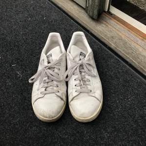 Vita adidas skor, stan smith med blåa detaljer, i strl 40. Väl använda därav slitningar etc. Köpare står för ev. frakt.