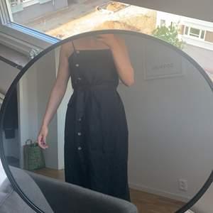 Svart klänning med knappar längst sidan!