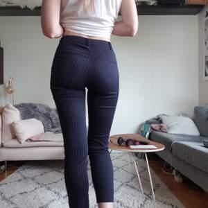 Kostymiga byxor från H&M. Mörkblå med vita smala ränder. Dragkedja på sidan och liten slits på utsidan av ankeln. Superbra skick, säljes pga för korta på mig (är 1,76) 😪