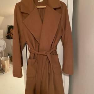 Lång Beige/camel kappa, tjockt ull-liknande material. Använd fåtal ggr och därav mycket bra skick.