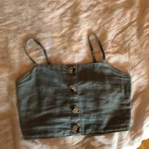 Ett kort turkost linne i linnetyg med knappar och resår i ryggen, tyvärr för litet för mig men superfint till sommaren